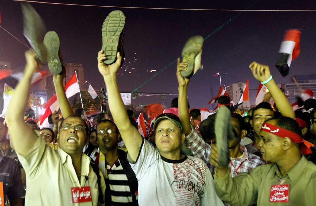 Anti-Mursi demonstranter viftar med skor i ilska efter presidentens tal på tisdagen.