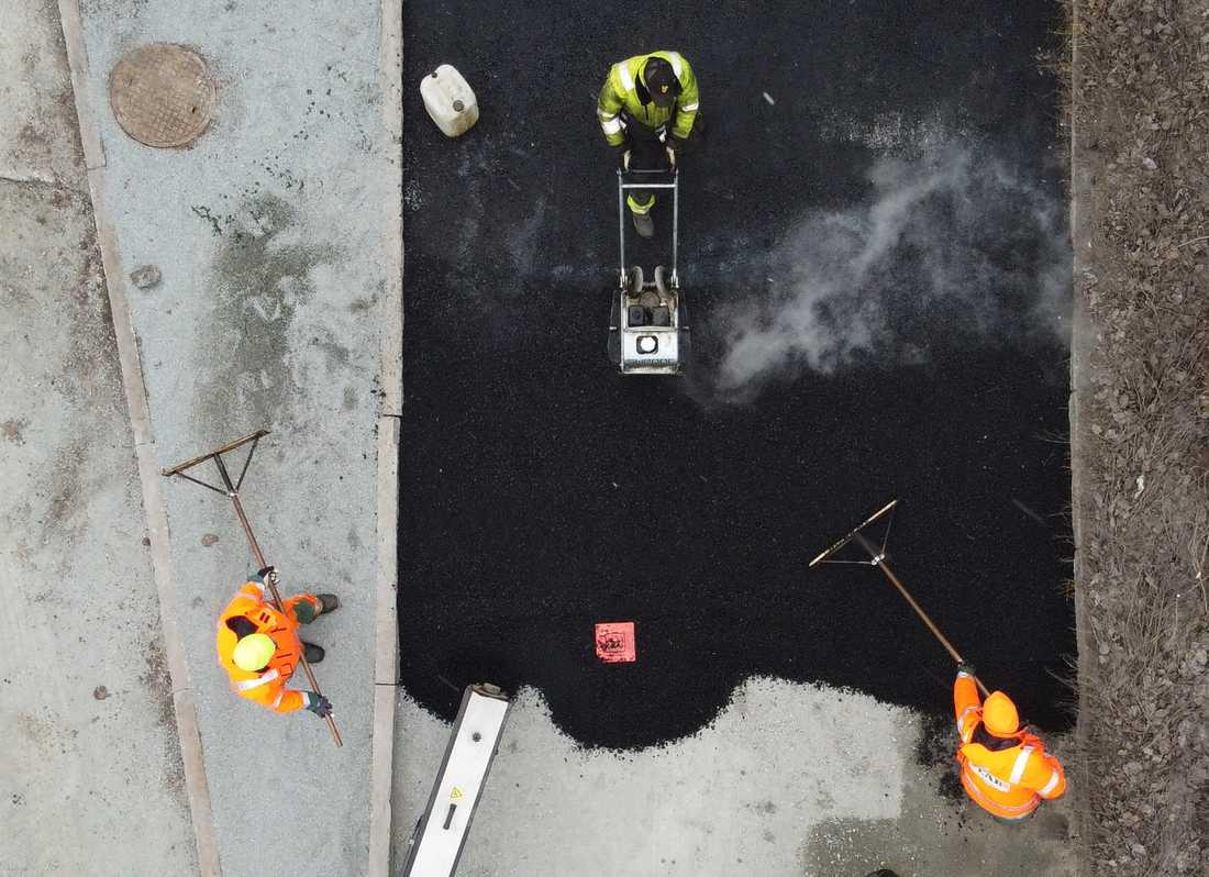 Vägarbetare lägger asfalt på en gata under ett gatuarbete i Enköping. Arkivbild.