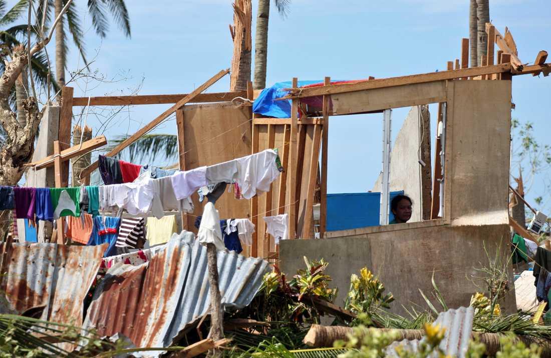 En kvinna sitter vid bråtet som nyligen var hennes hus i staden Daanbantayan i Cebuprovinsen.