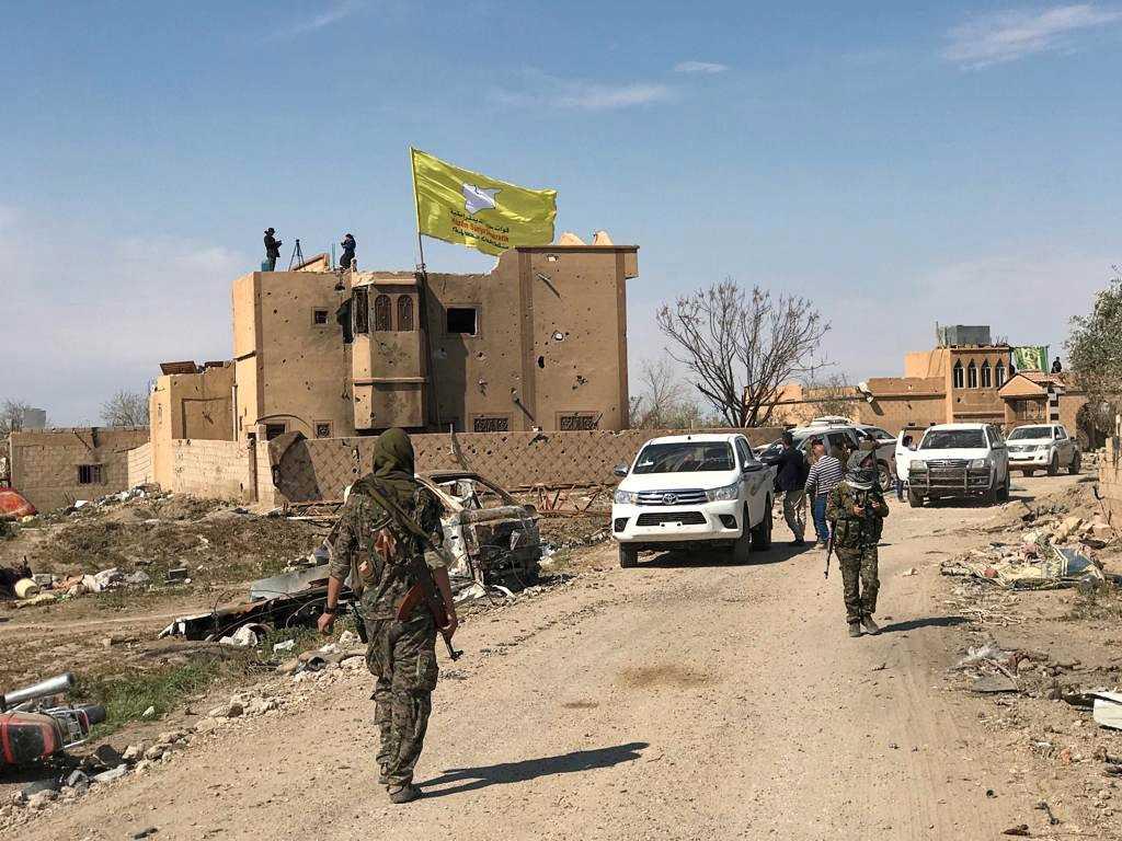 En SDF (Syrian Democratic Forces) flagga vajar i vinden på en byggnad i Baghouz i Syrien.