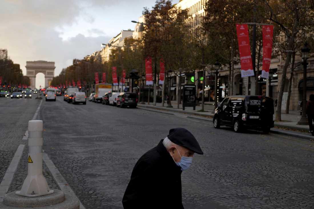 En äldre man med munskydd korsar paradgatan Champs-Élysées i Paris. Frankrike planerar att lätta på restriktionerna i tre steg.