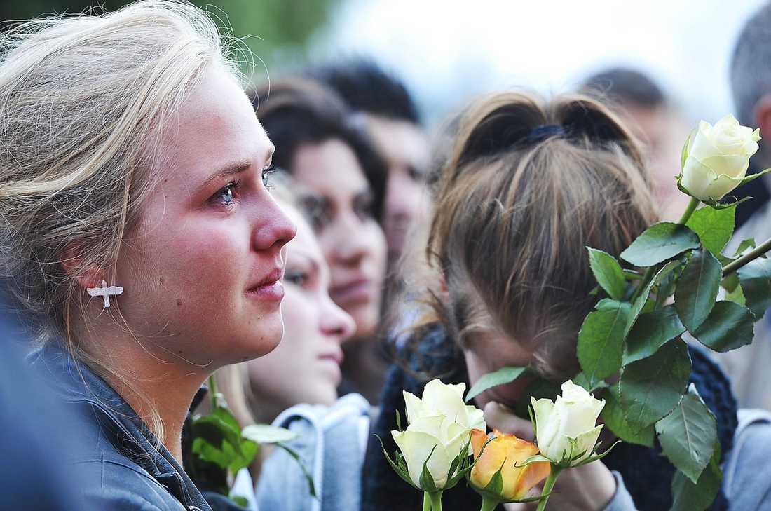 TÅRAR Två unga flickor med rosor i händerna gråter medan de lyssnar på talen och musiken.