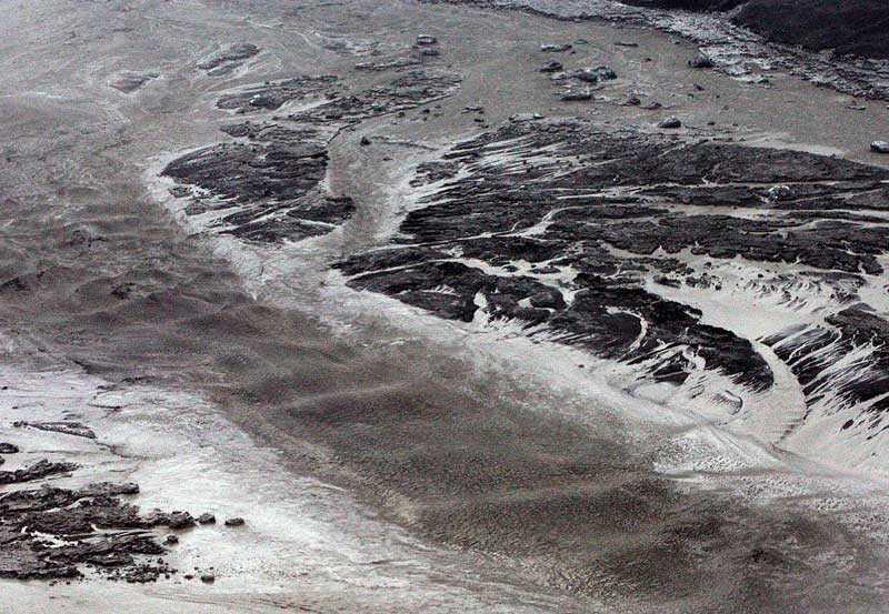 Askmolnet som sprids från vulkanområdet över norra Europa har färgat vattnet vid den islänska kusten svart.