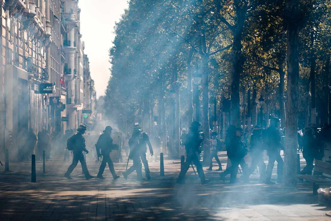 Kravallpolis på Champs-Élysées efter att tårgas använts mot demonstranter i Paris.