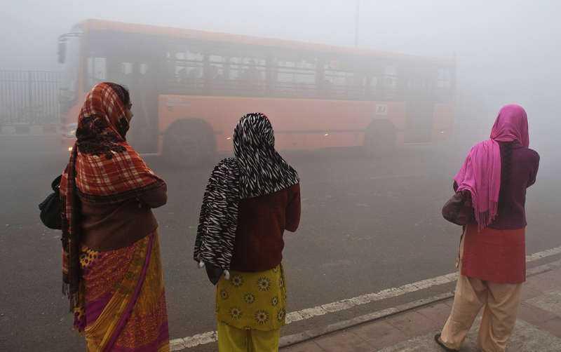 Indiska pendlare väntar på en buss i den förorenade luften i New Delhi.