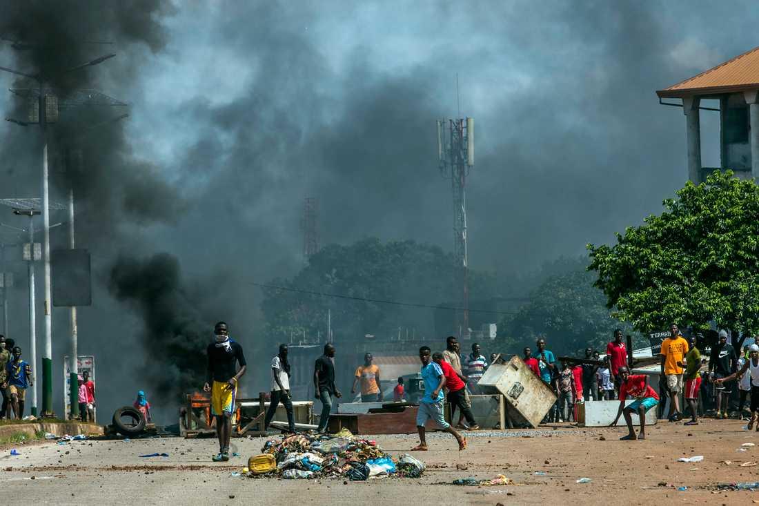 Anhängare till oppositionsledaren Cellou Dalein Diallo kastar sten mot polisen i Guineas huvudstad Conakry.