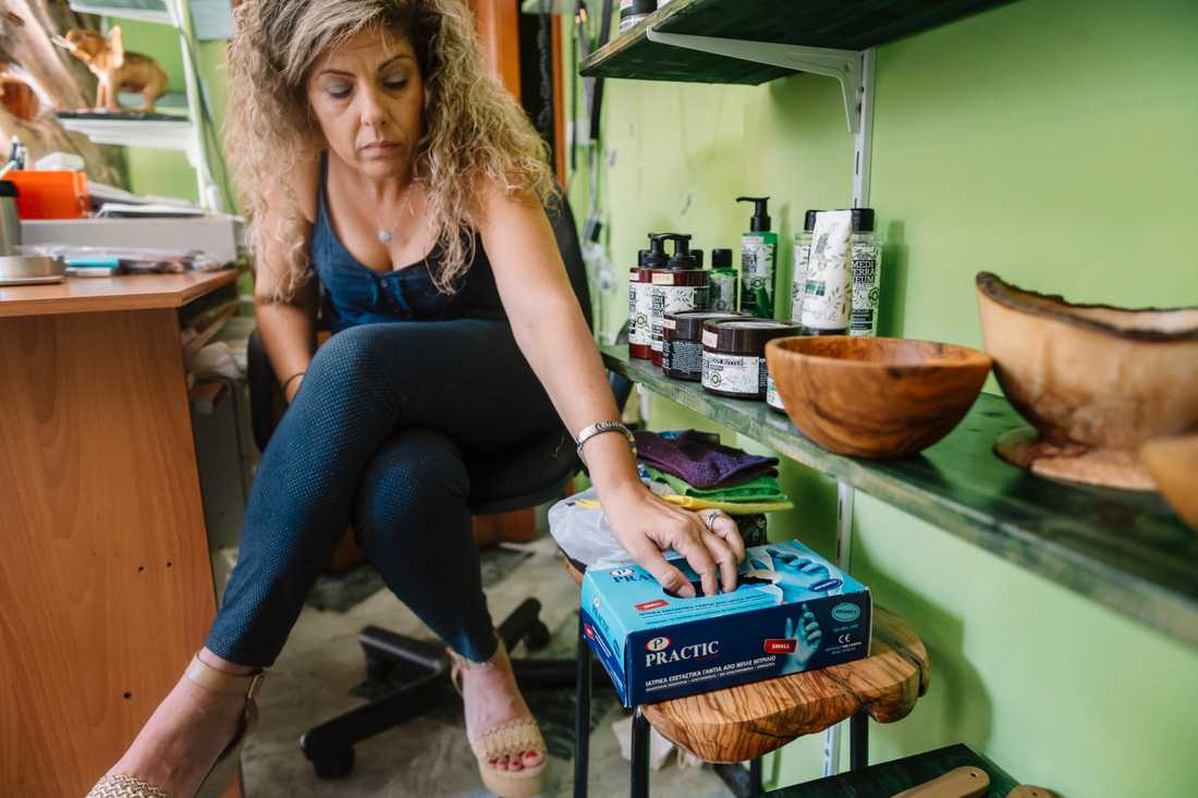 """Sofia Mitropoulou måste ha munskydd, plasthandskar och handsprit tillgängligt i sin lilla butik. """"Men jag är inte rädd för viruset, så jag har inte munskyddet på mig. Jag tycker det blir svårt att andas"""" säger hon."""