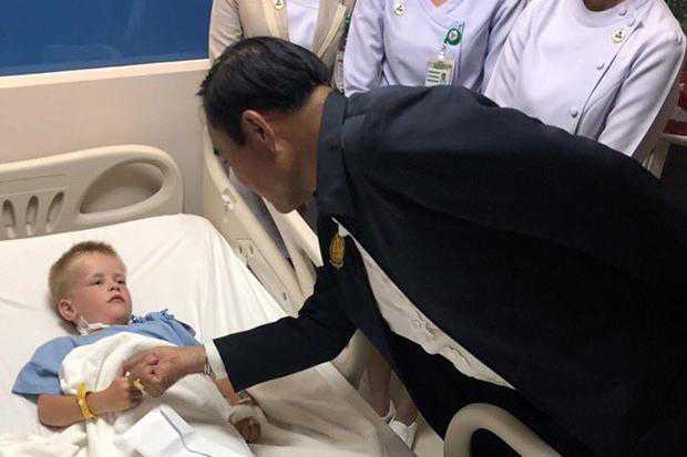 Thailands premiärminister Prayut Chan-o-cha besöker en finsk pojke som har blivit attackerad av hundar på Ao Nang Beach.