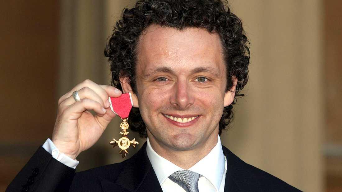 Michael Sheen med medaljen han mottog av drottning Elizabeth II 2009 - och lämnade tillbaka.