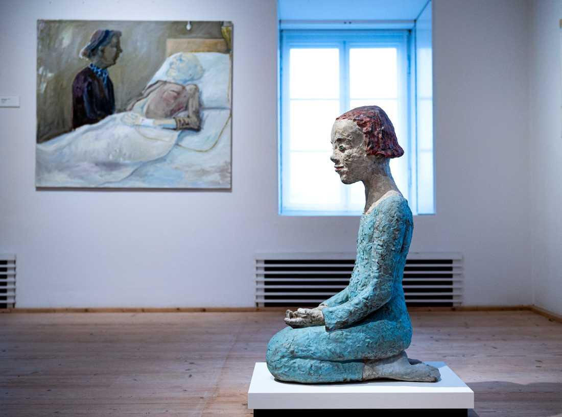 """Lena Cronqvists målning """"Sjukbädden"""" från 1975 visas tillsammans med den helt nygjorda bronsstatyn """"Knäböjande flicka"""" från 2020."""
