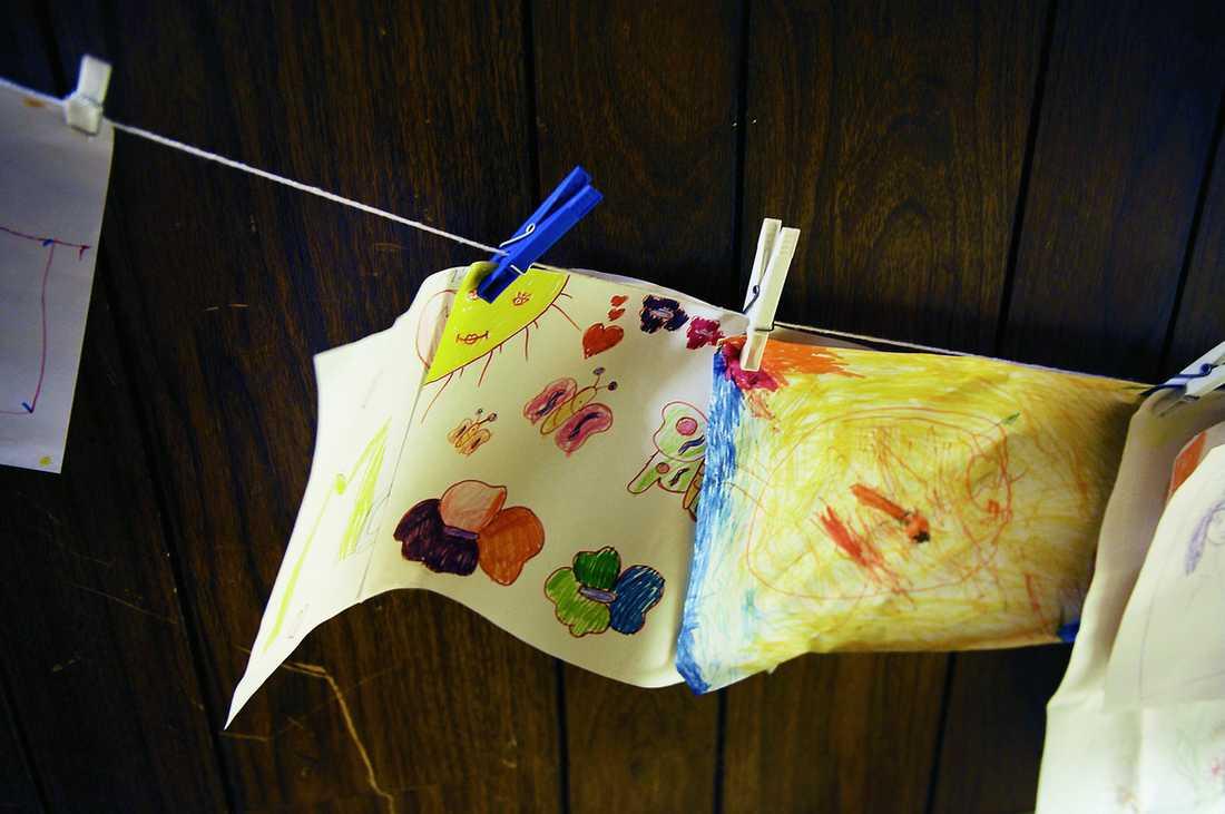 """Fjärilar, blommor, hjärtan och en sol. På väggen ovanför trappan som leder ner till källaren hänger de gömda barnens teckningar. Genom att måla och rita berättar barnen om sina liv och framtidsdrömmar. """"Barn som varit utsatta för övergrepp behöver måla för att förstå och bearbeta sina känslor och upplevelser"""", berättar Kristina. Hon sitter ofta med vid ritbordet och försöker få barnen att förklara vad som finns på teckningarna."""