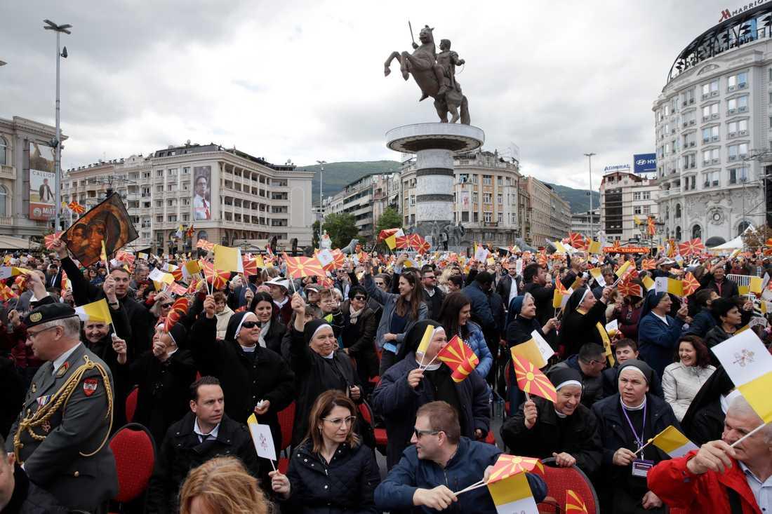 Människor välkomnar påve Franciskus när han anländer för att delta vid en mässa i Skopje.