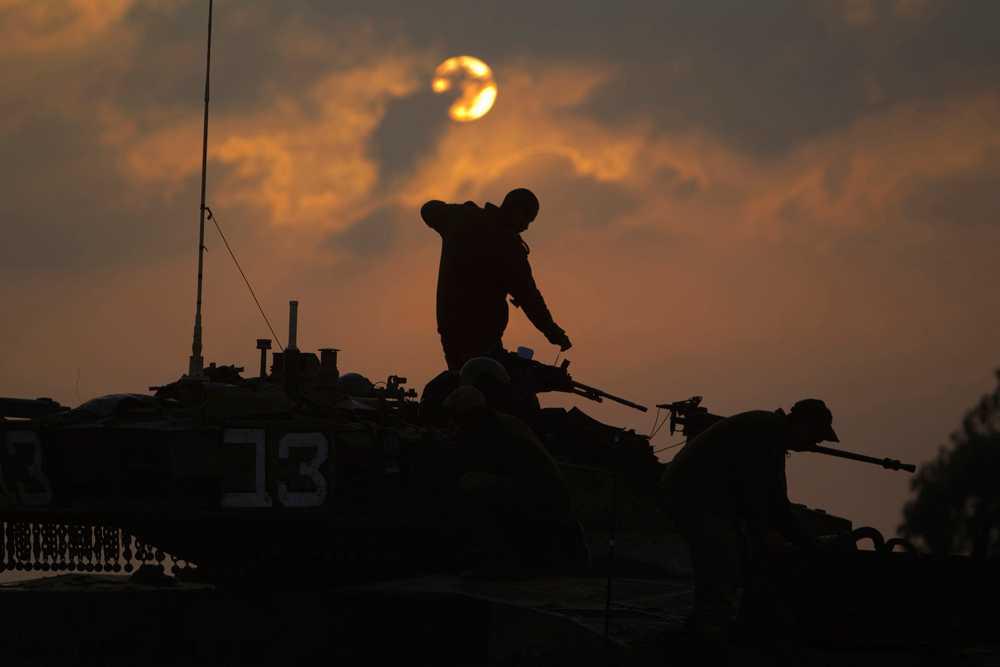 Israeliska soldater på en pansarvagn vid gränsen till Gaza.