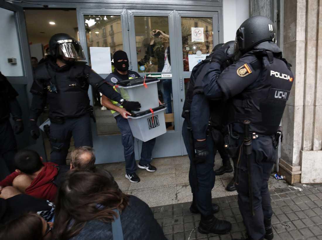 Spansk polis tar hand om valurnor i en vallokal i Barcelona.