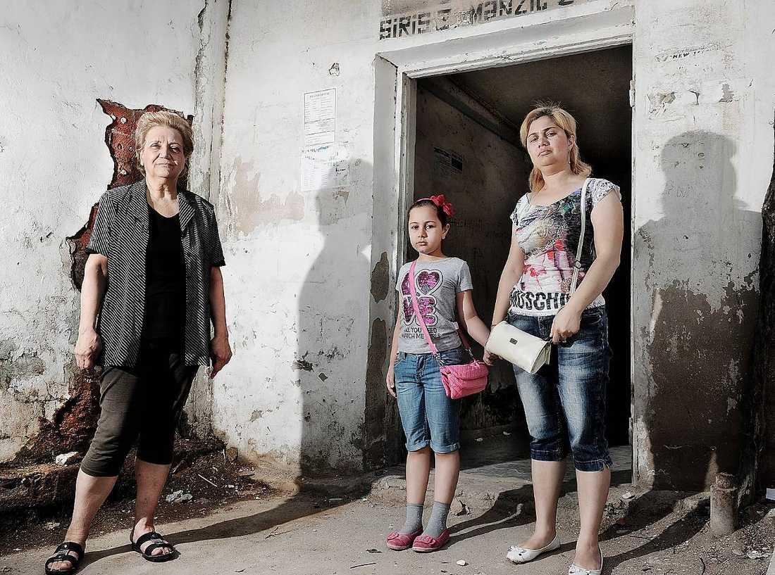 bytte havet mot mögel Här står Tatyana, 68, tillsammans med väninnan Aytan, 37, och hennes dotter Azamat, 9, utanför Tatyanas nya hem. Det är sämre standard och en bra bit från den gamla lägenheten vid Kaspiska havet. Hit tvingades de när Baku skulle totalrenoveras.