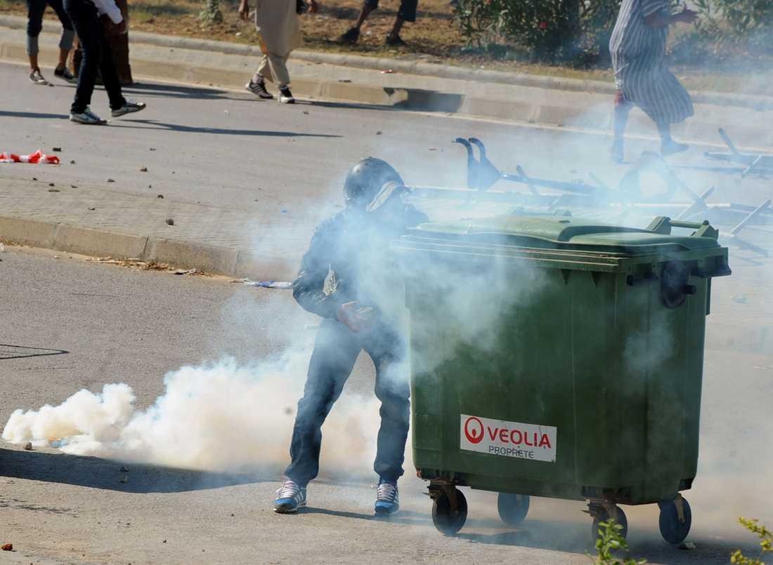 En demonstrant tar betäckning bakom en soptunna när kravallpolis skjuter tårgas under protesterna i Tunis.