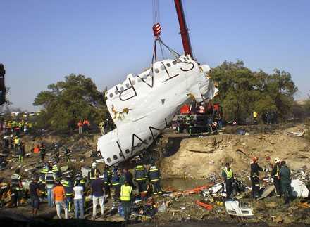 En kran lyfter bort vrakdelar från platsen där planet kraschade när det var på väg att lyfta från Barajas-flygplatsen i Madrid.