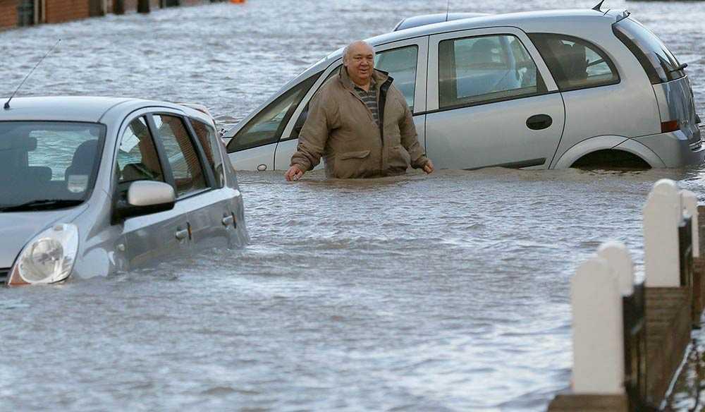 En man vadar i vatten upp till midjan på en gata i Rhyl, Wales. Staden har drabbats av kraftiga översvämningar till följd av ovädret.
