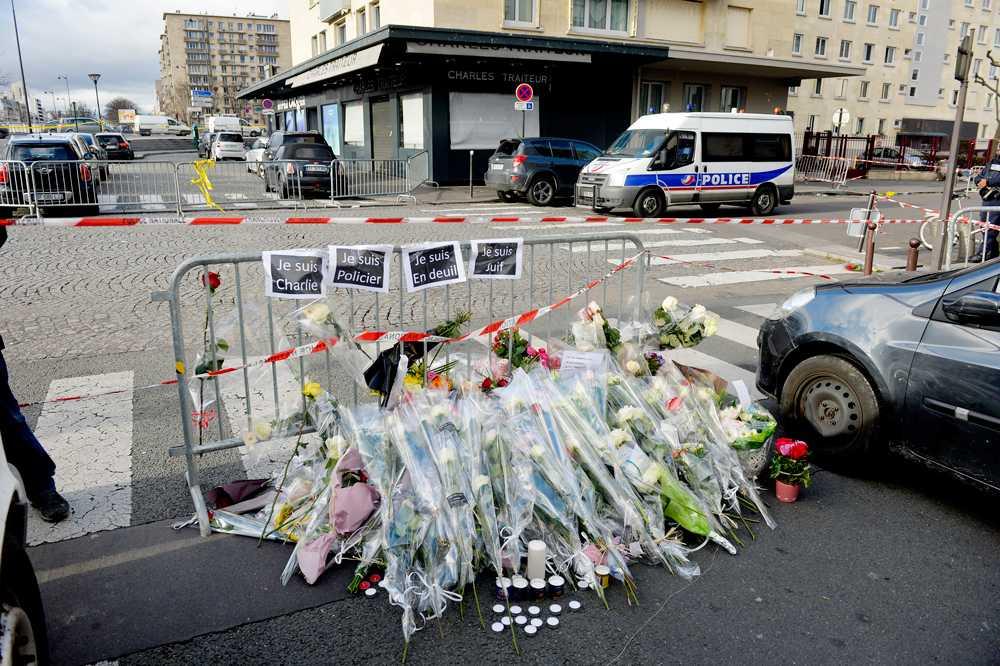 Människor har lagt blommor vid platsen där blodiga gisslandramat i Paris utspelade sig.