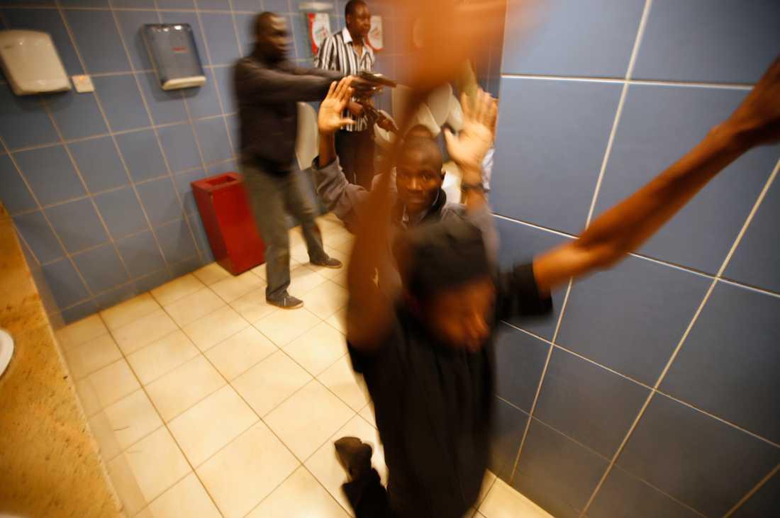 Beväpnad polis visiterar kunder som tagit skydd inne i gallerians toalett.