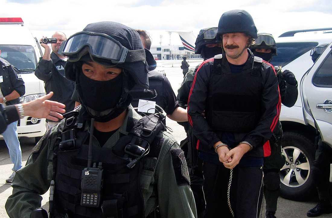 Viktor Bout lämnar Thailand eskorterad av tungt beväpnad polis och klädd i hjälm samt skyddsväst.
