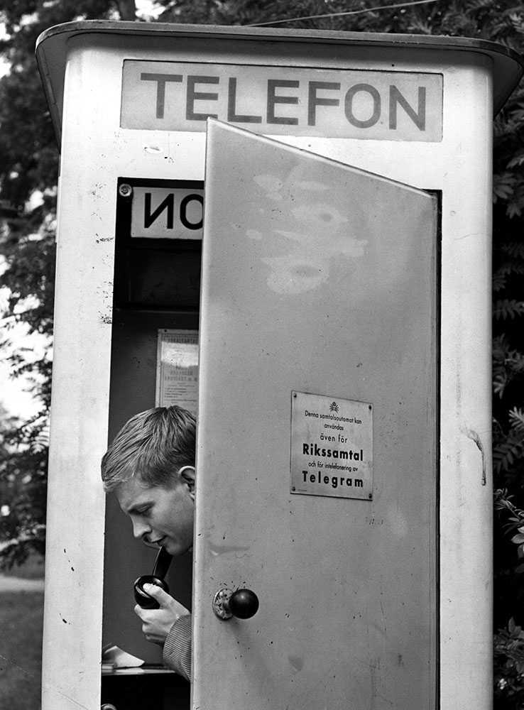 Ung man i en telefonkiosk i Kärrtorp 1963.
