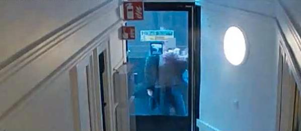 En kvinna trycker sig mot en dörr och undkommer precis lastbilens framfart.