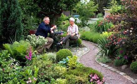 fikastund Gunnel och Alf Nordberg på sin härliga uteplats. Framför fikahörnan har de gjort en surjordsplantering med rhododendron, ljung och lingon.