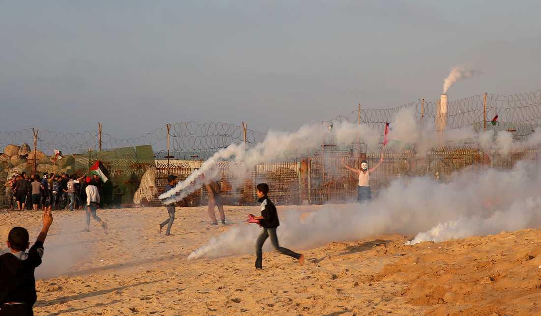 Demonstranter flyr undan tårgas vid en demonstration vid gränsstängslet mellan Israel och Gaza. Arkivbild.