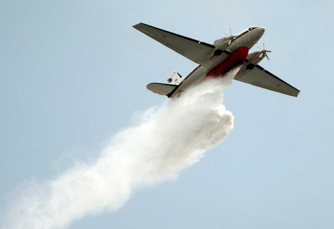 Ett plan från Thailands flygvapen sprayar vatten över Bangkok för att rensa luften.