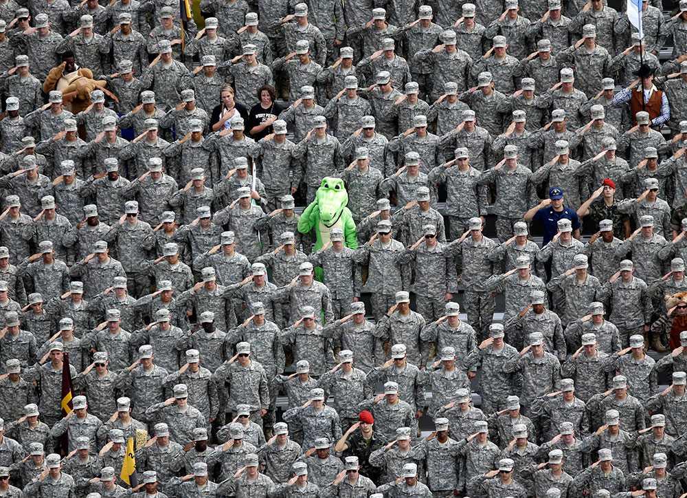 En amerikansk officersaspirant utklädd till alligator gör honnör tillsammans med sina kamrater under nationalsången som föranledde collagematchen mellan Army and Stanford.