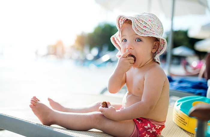I skuggan. Barn, oavsett ålder, bör undvika att vara i direkt sol mitt på dagen när den lyser som starkast.