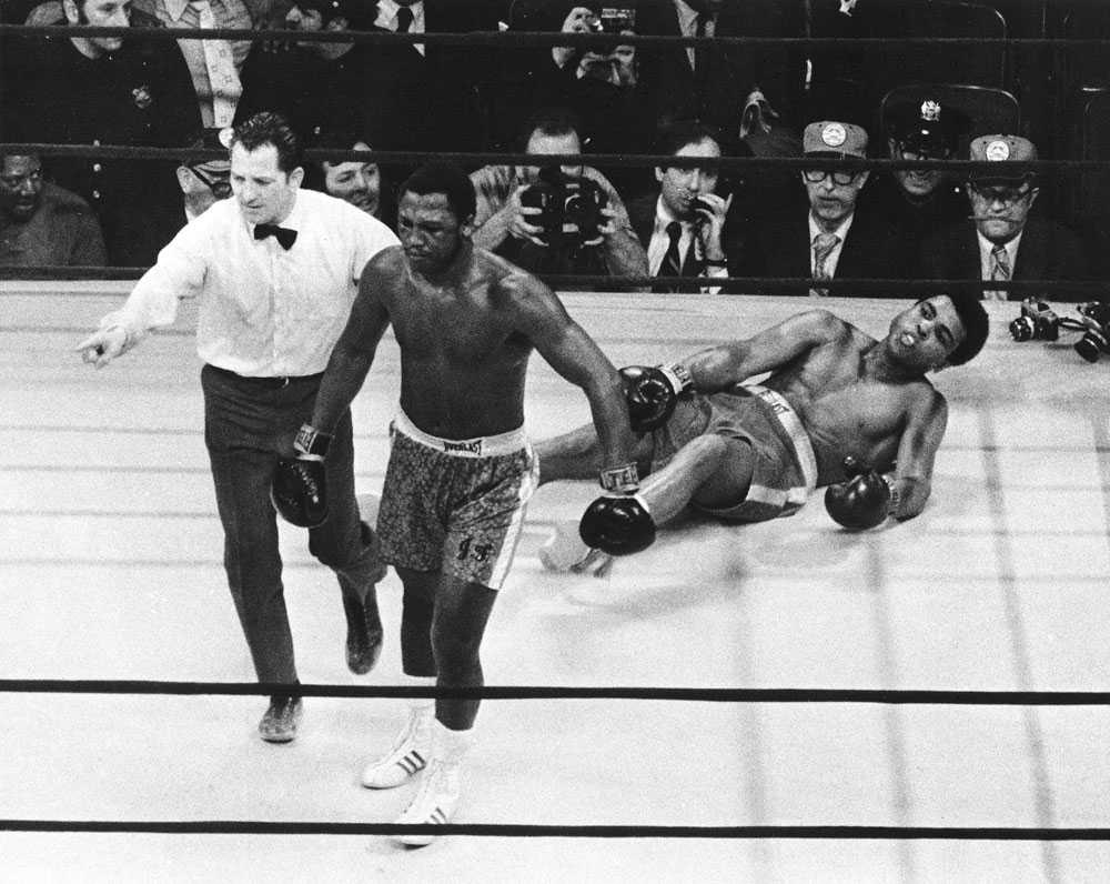 """OVANLIG SYN Muhammad Ali ligger ner efter en hård vänster från Joe Frazier. Titelmatchen i Madison Square Garden 1971 döptes till """"The Fight of the Century"""". Båda boxarna var obesegrade fram till matchen, bara Frazier efter den."""