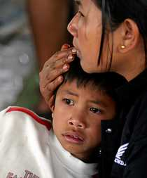 En mamma i skyddslägret tröstar sin son.