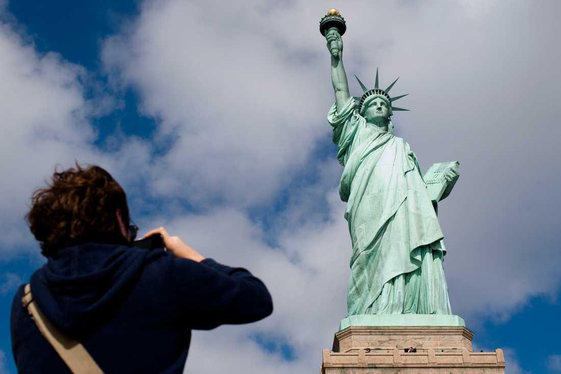 En av de 62,5 miljoner turisterna i New York förra året tar en bild av frihetsgudinnan.