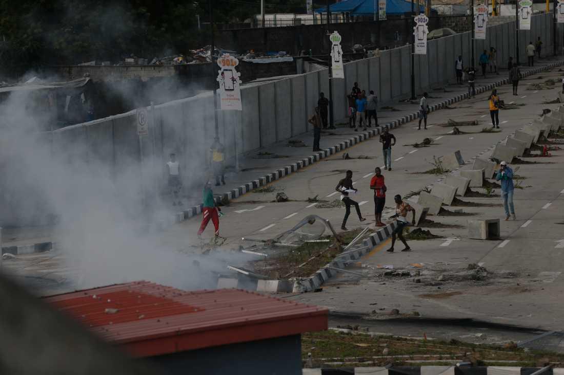 Demonstranter tar till flykten då polis sätter in tårgas för att skingra protester i Lagos på onsdagen.