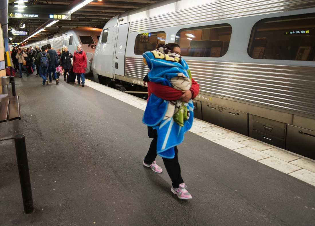 En kvinna med ett sovande barn anländer till Stockholm med tåget från Malmö/Köpenhamn under hösten 2015, då många flyktingar kom till Sverige. Arkivbild.