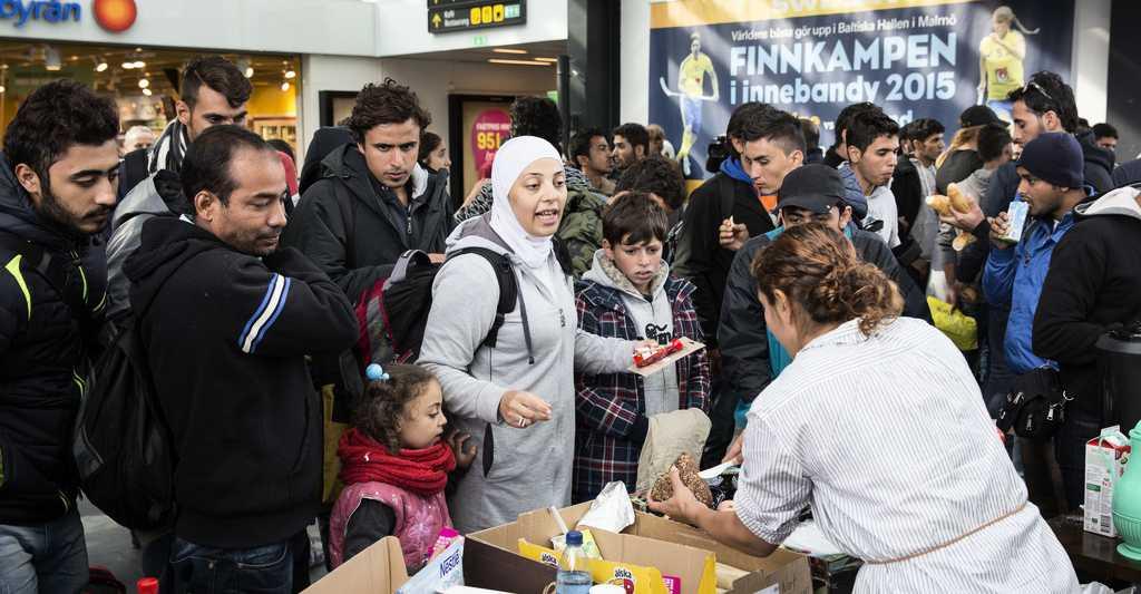 Flyktingar får mat och dryck på Malmö Centralstation i september 2015.