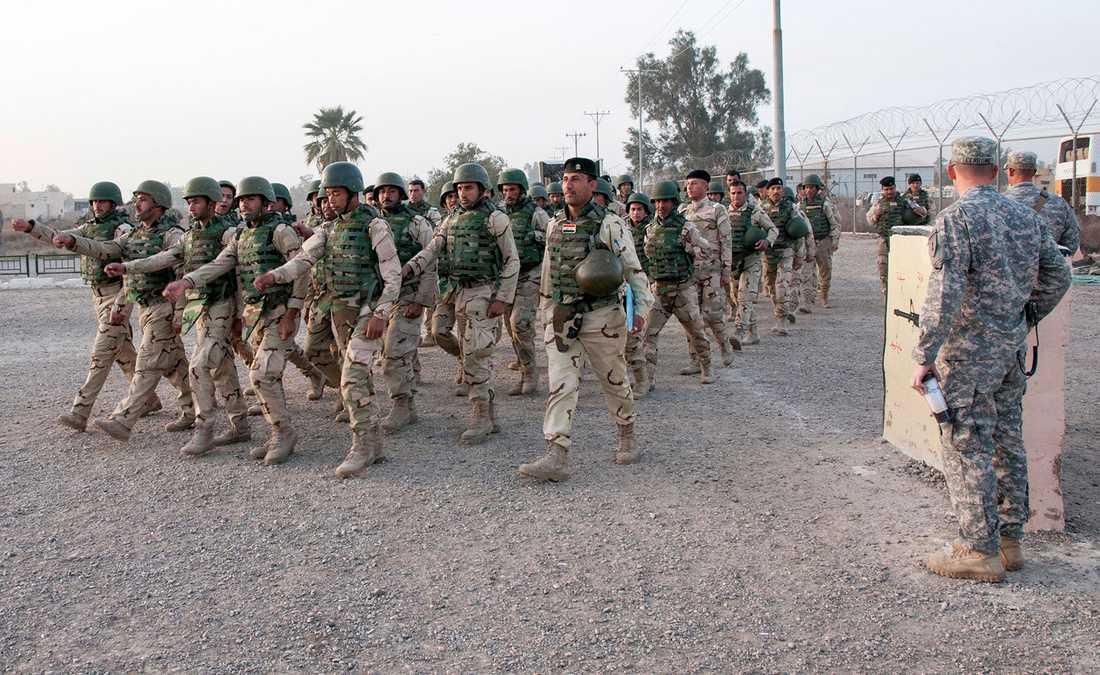 Irakiska soldater marscherar förbi amerikanska officerare.