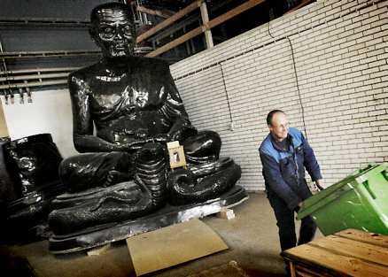 En fyra meter hög munkstaty står i en industrilokal i Fredrika i väntan på att templet ska bli färdigt.