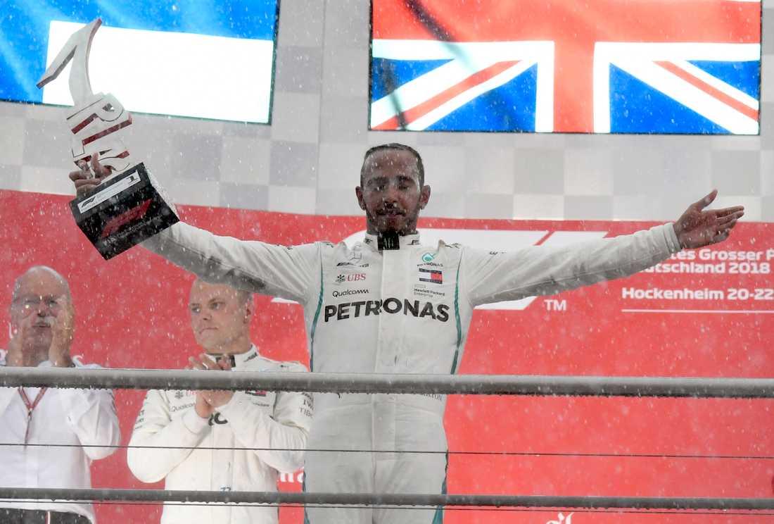 Regnet vräkte ner efter målgången. En blöt men lycklig Lewis Hamilton kunde fira på prispallen.