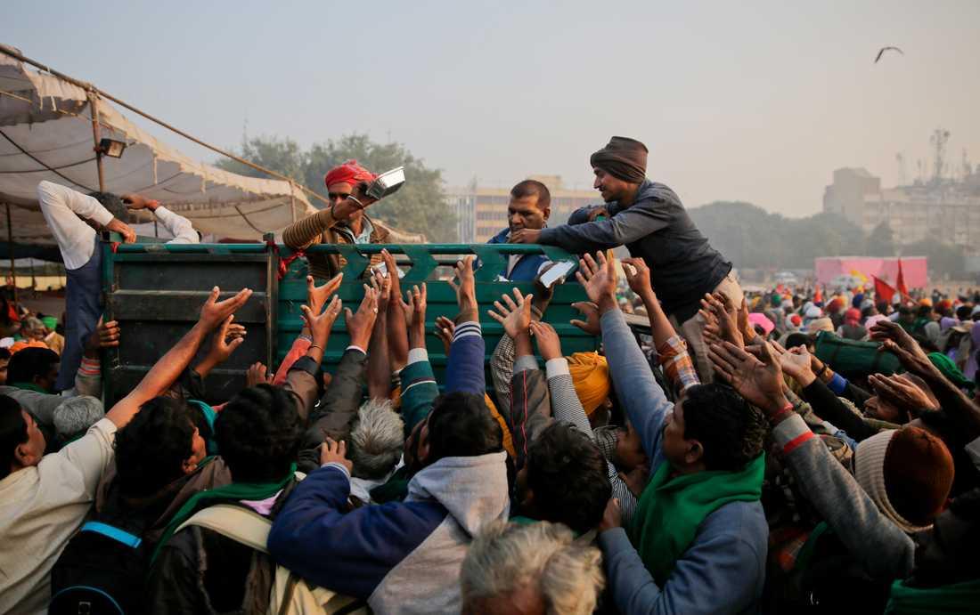 Frivilliga delar ut frukost till några av de tiotusentals lantbrukare som väntas demonstrera i Dehli.