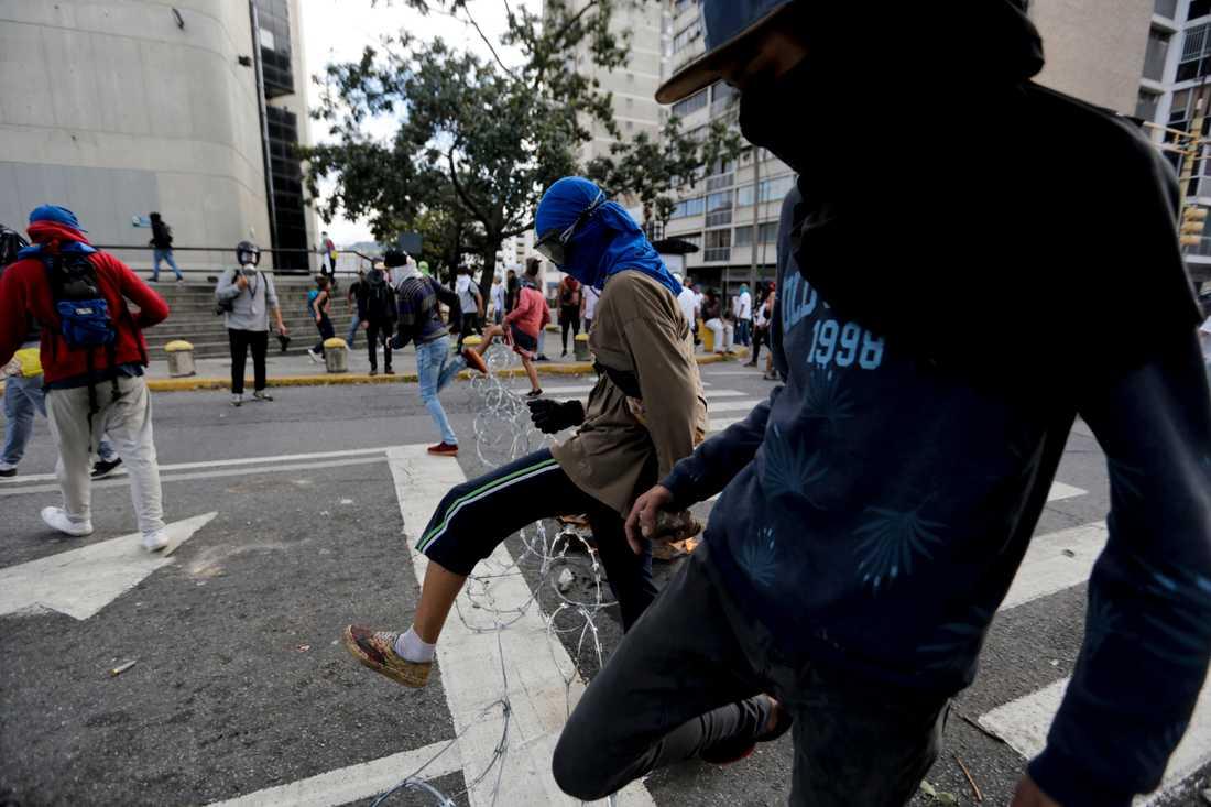 Demonstranter hoppar över en barriär av ståltråd i Caracas.