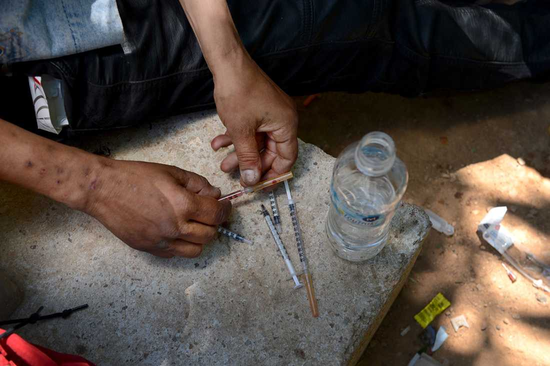I parken mellan Atens kulturhus och universitetets juridiska fakultet pågår torghandel med heroin. En försäljare utan tänder håller upp en färdig spruta till försäljning, priset är lågt, fem euro för en tripp.