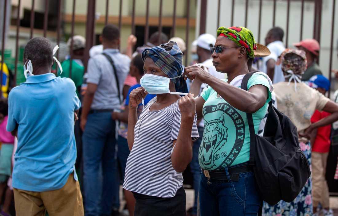 En kvinna får hjälp med sitt munskydd i Pétionville nära Haitis huvudstad Port-au-Prince.
