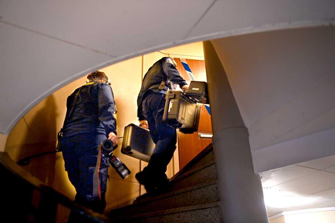 Tekniker på väg in i lägenheten där den nu vuxna sonen ska ha hållits inspärrad.
