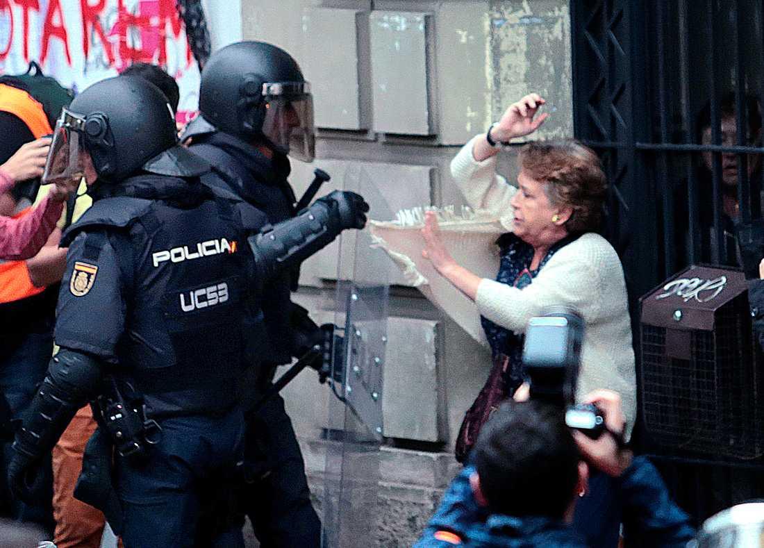 Kravallpolis tar tag i en kvinna i närheten av en vallokal.