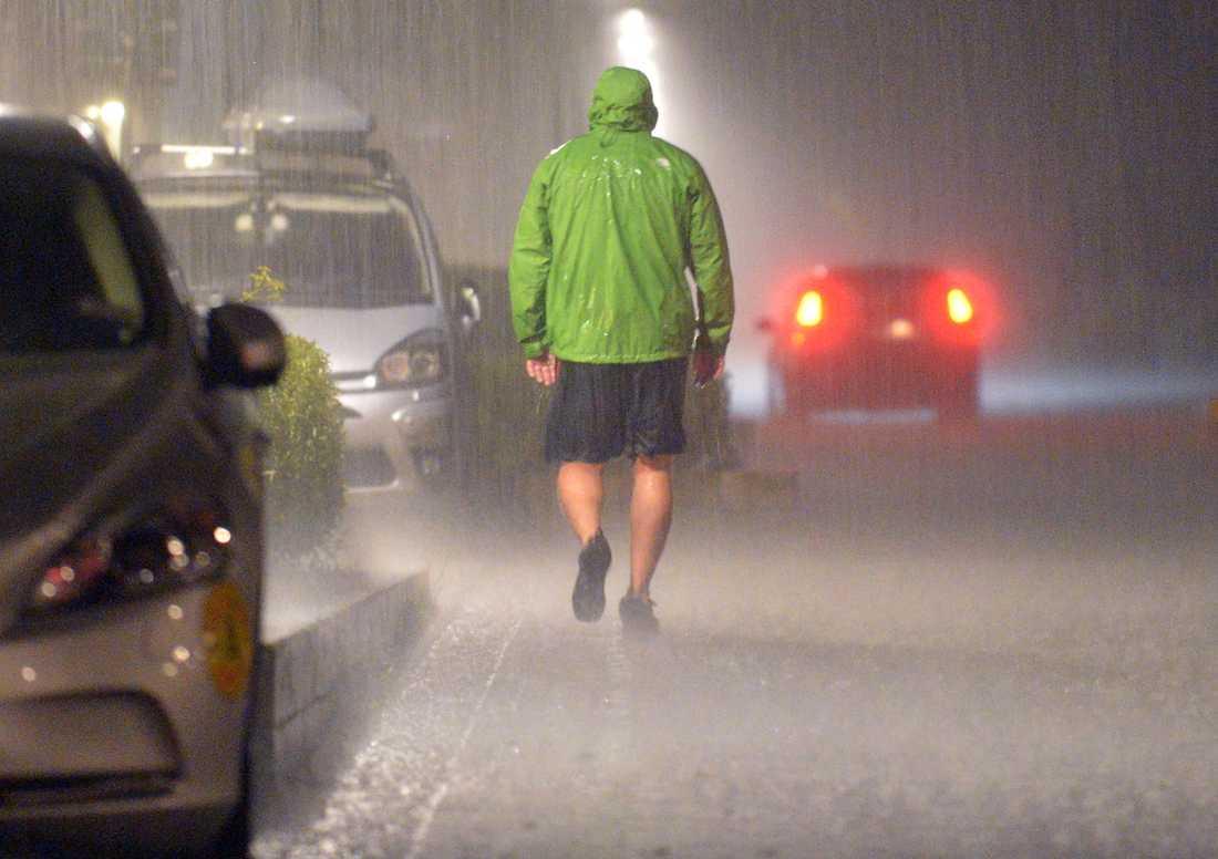 Mycket blöt man på promenad i Västra Hamnen under kraftiga åsk- och regnvädret med skyfall den 3 augusti 2014.