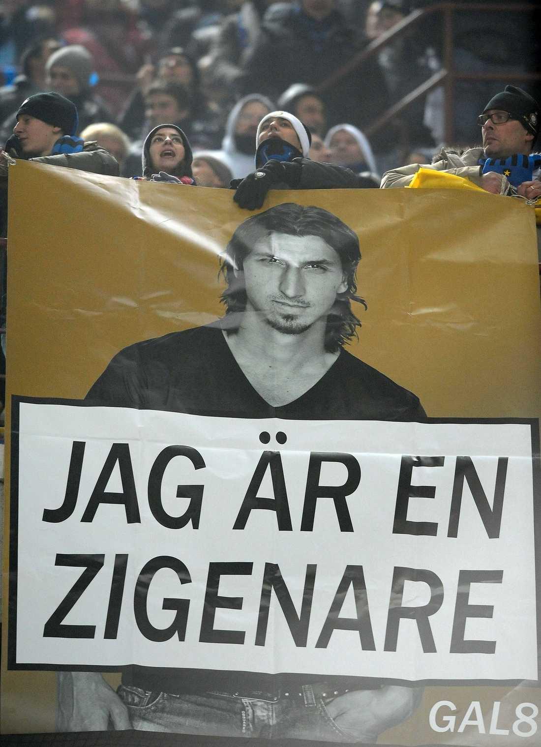 """BANDEROLLEN SIGNERAD """"GAL8"""" Bilden är tagen den 15 januari 2012 i derbyt mellan Milan och Inter när Zlatan Ibrahimovic spelade för den förstnämnda klubben. Banderollen är gjord som omslaget till Zlatan Ibrahimovics självbiografi, men där texten bytts ut till """"Jag är zigenare"""". Längst ner till höger har den signerats med """"GAL8"""" och högst upp syns, enligt uppgifter till Sportbladet, Jonas Galotta som är en av de nya makthavarna runt AIK Hockeys verksamhet."""