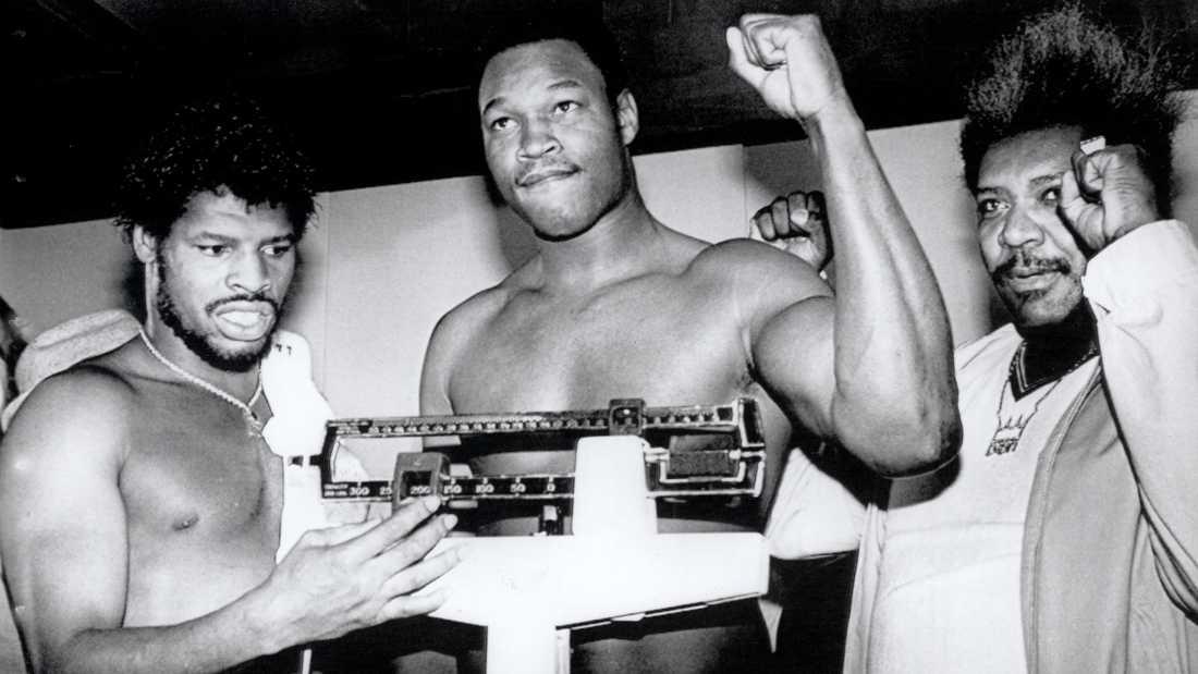 Larry Holmes (1949-) (mitten) under invägningen inför en titelmatch mot Leon Spinks (1953-) i juni 1981. Holmes innehade WBC-titeln 1978-1983, The Ring Heavyweight Champion-titeln 1980-1985 och IBF-titeln 1983-1985. Till höger ökände promotorn Don King.